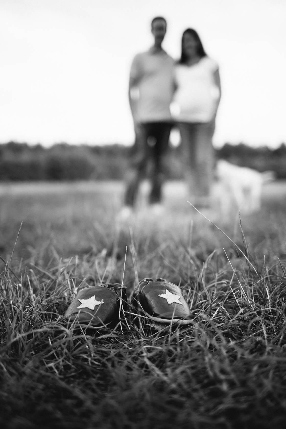Entspanntes Paarshooting und Babybauch Shooting. Kleine Schuhe auf der Wiese.